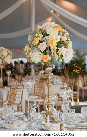Table set for an event party or wedding reception, focus on centerpiece bouquet - stock photo