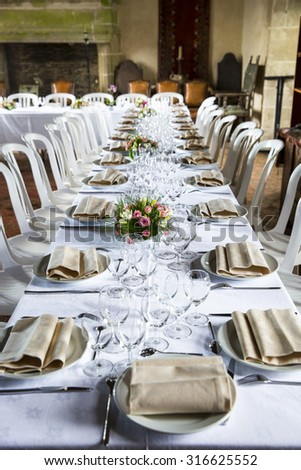 Table set for an event party or wedding reception in a old medieval castle room - stock photo