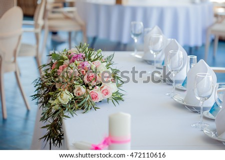 Table set for an event party or wedding reception. Large floral arrangement of roses and peonies