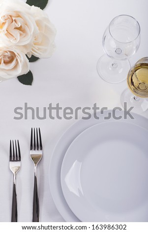 Table set for celebration with roses - stock photo