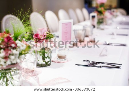Table set in soft pink and white for wedding or event party. Luxury decoration for celebration, with give away for guests