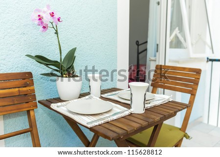 Table set on terrace for breakfast - stock photo