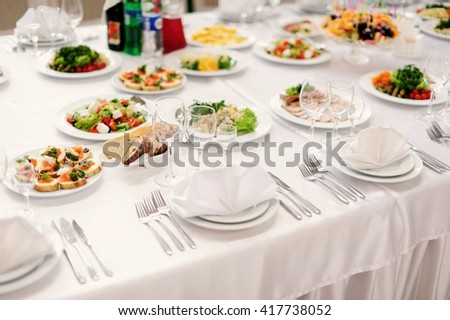 table set service with silverware and glass stemware at restaurant before party