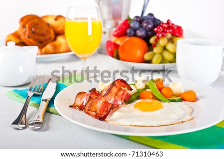 Table set up for breakfast: fruits, pastry, fried egg with vegatables and bacon. - stock photo