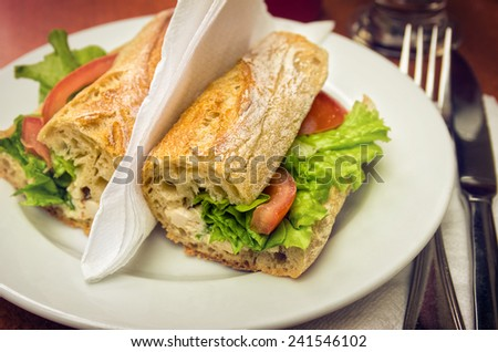 Table set with a sandwich with cheese, lettuce and tomato - stock photo