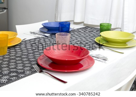 Table set with colorful dishes in the home kitchen - stock photo