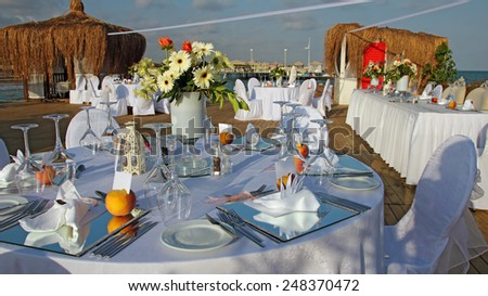 Table Setting at a Luxury Wedding Reception. Wedding reception place ready for guests. Luxury wedding dining table setting outdoors. Wedding Reception Dining Tables by the Sea. - stock photo