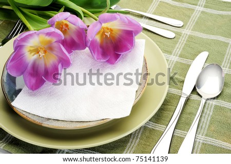 Table setting at restaurant with tulips and message - stock photo