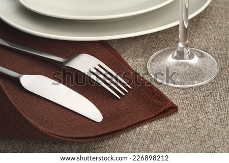 Table setting. Cutlery set with fork, knife, plate and glass on brown linen napkins and tablecloth. - stock photo