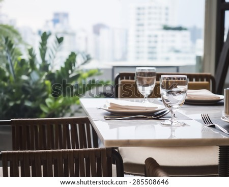 Table setting dinner Restaurant interior with garden and skyline view - stock photo