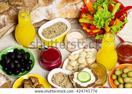 Table setting for a summer picnic - vegetables and mushrooms, olives, meats, sausages and pate, a variety of sauces. Bread and juice. Selective focus. - stock photo