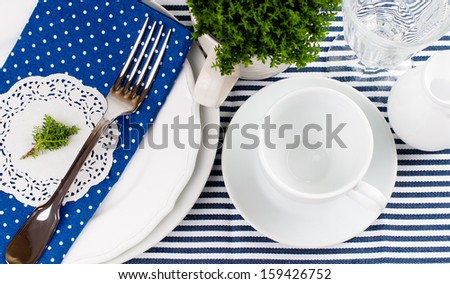 Table setting for breakfast with napkins, cups, plates in blue on a white background isolated - stock photo
