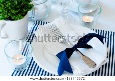 Table setting for breakfast with napkins, cups, plates in navy blue tones on a white background isolated - stock photo