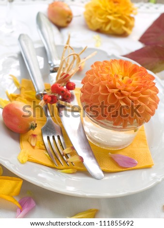 Table setting in orange and yellow tones, selective focus - stock photo