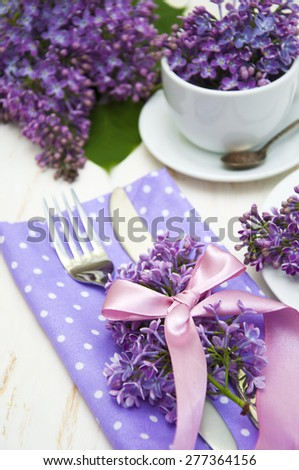 Table setting in purple colors, decoration flowers fragrant lilacs on a white wooden board - stock photo