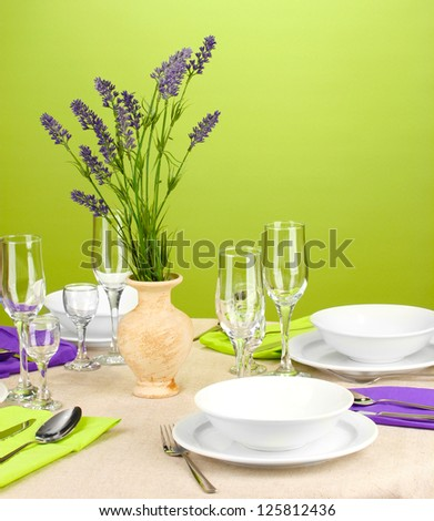 Table setting in violet and green tones on color  background - stock photo