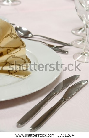 table setting Plate with napkin and cutlery at a dinner table - stock photo
