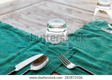 table setting, silverware and eating concept - close up of cutlery with glass and napkin on restaurant table - stock photo