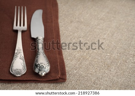 Table setting. Vintage fork and knife on brown napkin with linen tablecloth and copyspace. - stock photo