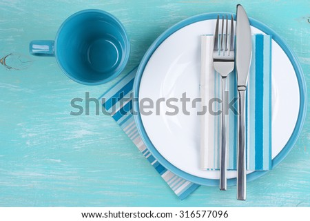 Table setting: white plate, fork and knife with napkins on aquamarine wooden table. Top view point. - stock photo