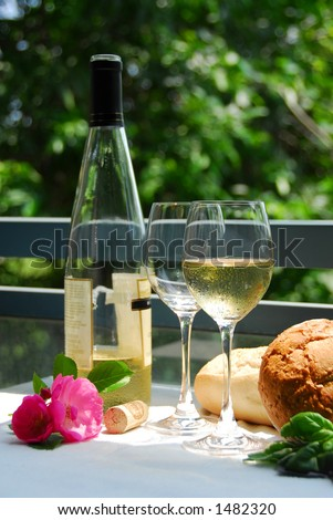 Table setting with chilled white wine and glasses alfresco - stock photo