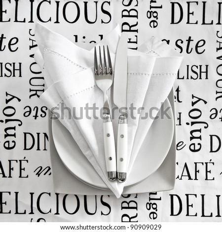 Table setting with cutlery and crockery on printed linen tablecloth - stock photo