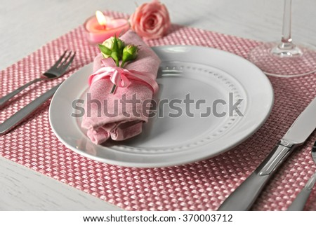 Table setting with dishes, napkin, cutlery and candle on pink background - stock photo