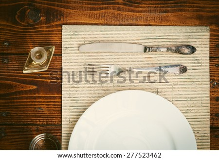 Table setting with empty plate- rustic wooden table - stock photo