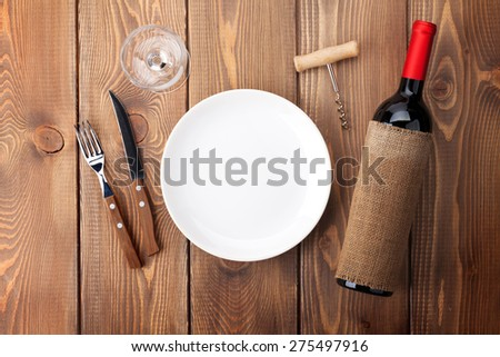 Table setting with empty plate, wine glass and red wine bottle. Top view over rustic wooden table background - stock photo
