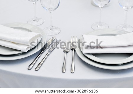Table setting with fork, knife, plates and napkin. - stock photo