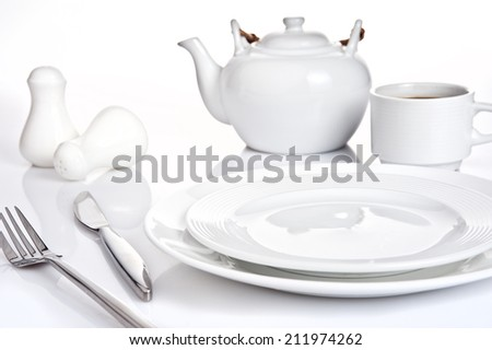Table setting with fork, knife, plates, cup of coffee and coffee pot.  Isolated on white background