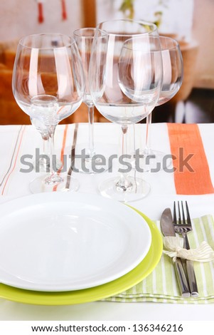 Table setting with glasses for different drinks on table on room background - stock photo