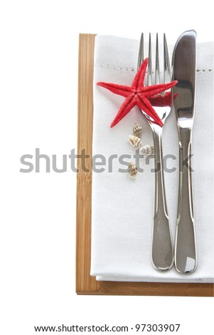 Table setting with knife and fork and starfish for a beach theme - stock photo