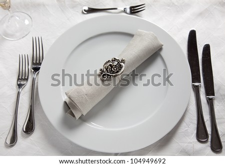 Table setting with plate, knives, forks napkin with ring on linnen tablecloth - stock photo