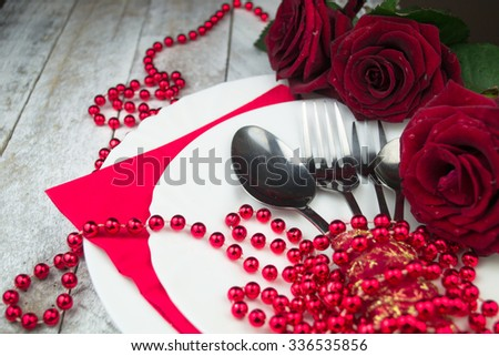 Table setting with red roses on white wood background - stock photo