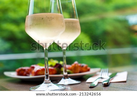 Table setting with two glasses of delicious cooled white wine with snack on background. Summer close-up. - stock photo