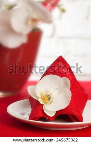 Table setting with white orchid flowers on red tablecloth