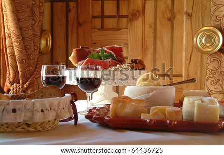 Table settings for a special occasion. Cheese assortment, bread and red wine in a glamorously styled room - stock photo