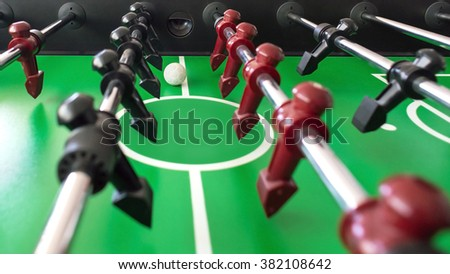 table soccer or table football, black and red figures on green. - stock photo