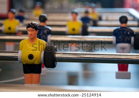 Table soccer players wearing blue and yellow jerseys - stock photo