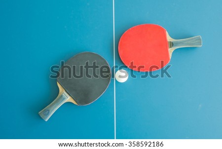 Table tennis bats and ball on a table with white vertical line. Concept of competition - stock photo