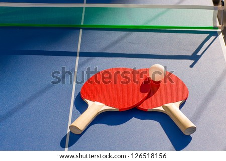 table tennis ping pong two paddles and white ball on blue board - stock photo