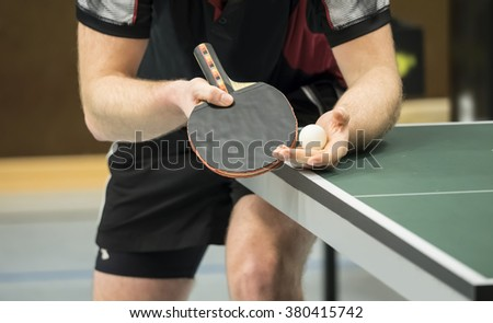 table tennis player serving - focus at the blade and ball / small depth of focus - stock photo