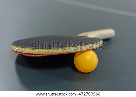 Table tennis racket on the table with the network and ball.