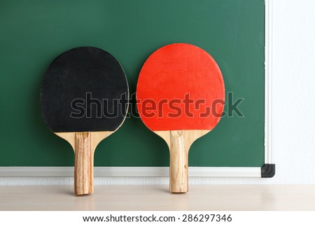 Table tennis rackets on blackboard background - stock photo