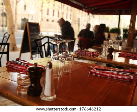 table with appliances and glasses in a Paris cafe - stock photo