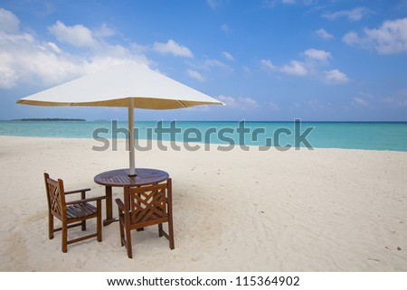 table with chairs at the beach with view to the turquoise sea and blue sky