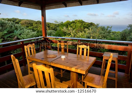 Table with chairs on terrace in sunset. Shot in Sodwana Bay campsite, KwaZulu-Natal province, Southern Mozambique area, South Africa. - stock photo