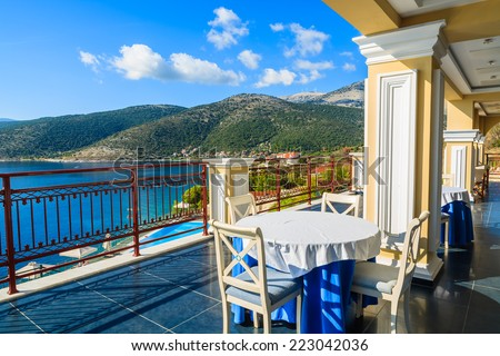 Table with chairs on terrace on coast of Kefalonia island in Agia Efimia village, Greece - stock photo