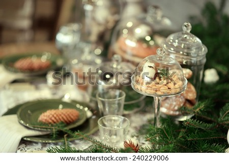 table with Christmas decorations and white large candles, glassware, green cones tree branch - stock photo